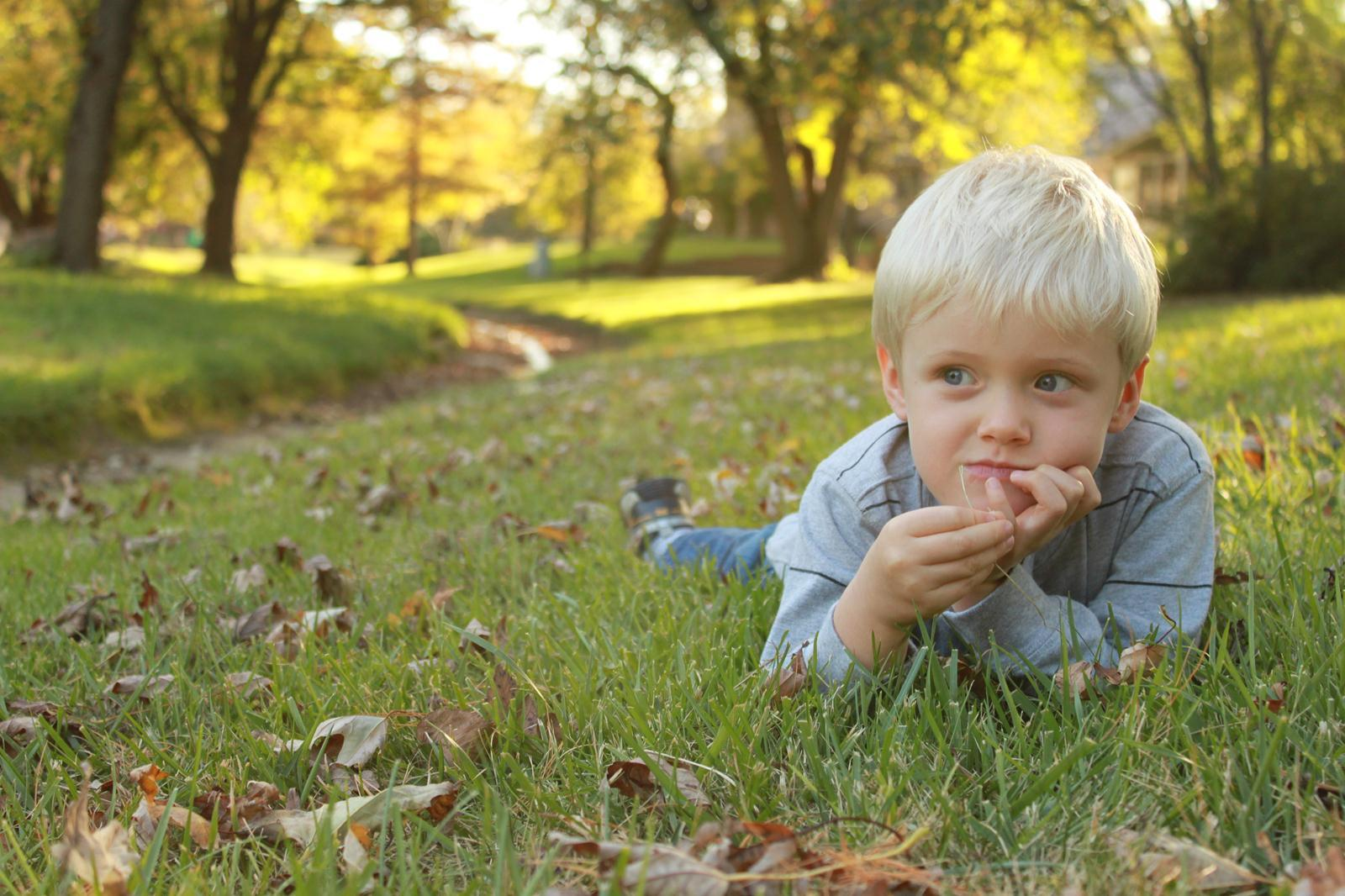 small child laying in the grass