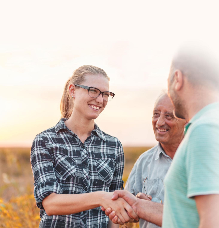 People shaking hands in a corn field