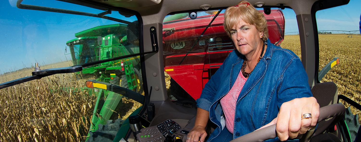 Woman driving harvester.