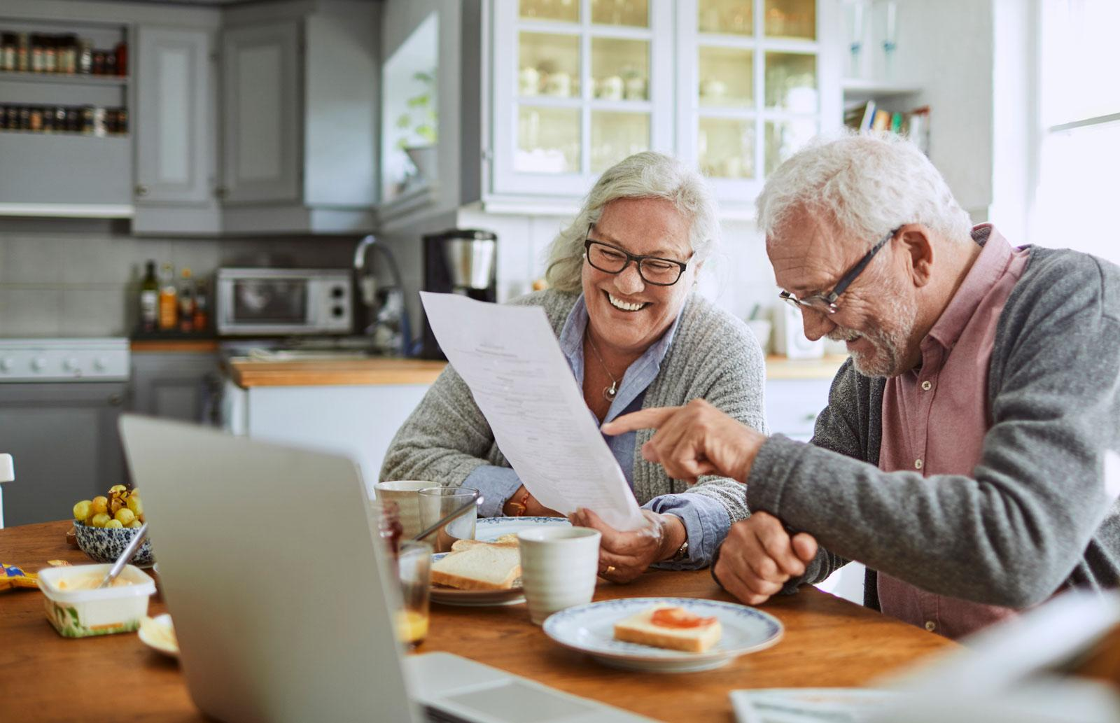 Older couple reviewing documents at the kitchen table